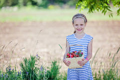 7 år hållande korg för gammal flicka som är full av jordgubbar Royaltyfria Bilder