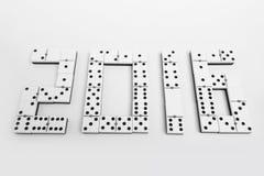 År 2016 i dominobrickastycken över en vit bakgrund Arkivbild