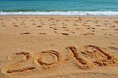 2019 ÅR inskrift som är skriftlig i den våta gula strandsanden Begrepp av att fira det nya året, parti på kusterna av royaltyfria foton