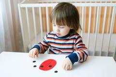 2 år litet barn gjord pappers- nyckelpiga Arkivbild