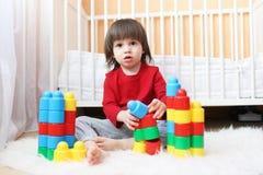 2 år litet barn med plast- kvarter Royaltyfria Bilder
