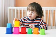 2 år litet barn som spelar plast- kvarter Royaltyfri Bild