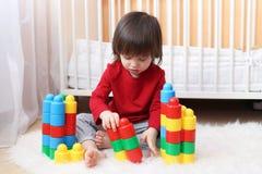 2 år litet barn som spelar plast- kvarter Fotografering för Bildbyråer