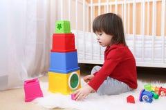 2 år litet barn som spelar plast- kvarter Arkivfoton