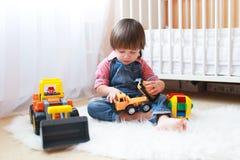 2 år litet barnpojke spelar bilar hemma Arkivbilder