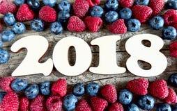 År 2018 med blåbär och hallon på en träbackgroun Arkivbilder