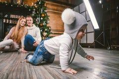 År och jul för familjferie nytt Ung caucasian son för familjmammafarsa 1 år att sitta på trägolvet nära spisjulträd royaltyfri fotografi