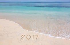 År 2017 på den sandiga stranden Arkivfoto