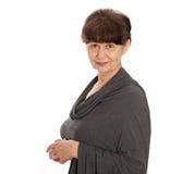 65 år stående för gammal kvinna mot av vit bakgrund Bra pensionsåldern se kvinnan som ler, London Arkivbild