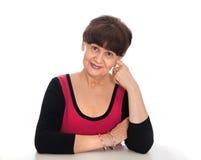 65 år stående för gammal kvinna mot av vit bakgrund Bra pensionsåldern se kvinnan som ler, London Arkivfoton