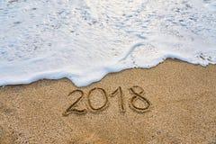Året 2018 passerade begreppet Vågen av skum tvättar bort inskriften 2018 som är skriftlig på sanden royaltyfria bilder