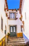 ÅrhundradeMediieval för smal vit gata 11th stad Obidos Portugal Fotografering för Bildbyråer