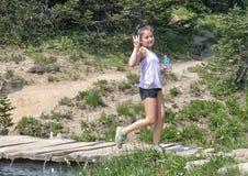 Årig Amerasian flicka för tio som går lyckligt över en bro i monteringen Rainier National Park, Washington arkivbild