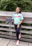 Årig Amerasian flicka för tio som poserar på en träbro i Washington Park Arboretum, Seattle, Washington royaltyfria foton