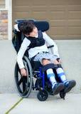 Årig biracial rörelsehindrad pojke sju i rullstol Arkivfoto