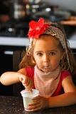 Årig en behandla som ett barn flickan i en röd blommahuvudbindel som hemma äter yoghurt av henne för frukost Arkivfoton