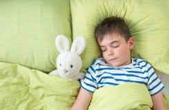 Årig en behandla som ett barn i sängen Arkivfoto