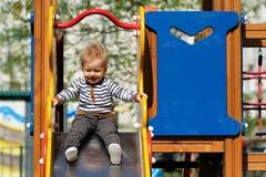 Årig en behandla som ett barn pojkelilla barnet på lekplatsglidbanan Arkivfoton
