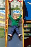 Årig en behandla som ett barn pojkelilla barnet som bär den gröna tröjan på lekplatsen Fotografering för Bildbyråer