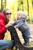 Årig en behandla som ett barn pojken i höst parkerar med hans moder Arkivfoton