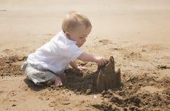 Årig en behandla som ett barn pojken som spelar på stranden med en sandslott Arkivfoton