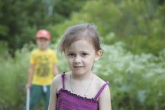 Årig flicka fyra och en pojke på skogbakgrund Arkivfoton