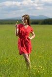 årig flicka 20 i en röd klänning med en gul blomma Arkivfoto