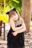 Årig flicka nätta tre i en kattdräkt, med en blomma i hennes hand Arkivfoton