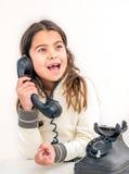 Årig flicka sju med den gamla tappningtelefonen för den vita backgrouen Fotografering för Bildbyråer
