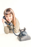 Årig flicka sju med den gamla tappningtelefonen för den vita backgrouen Arkivfoto