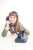 Årig flicka sju med den gamla tappningtelefonen för den vita backgrouen Arkivbild