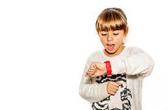 Årig flicka som åtta ser hennes klocka som förvånas på vilken tid Arkivbilder