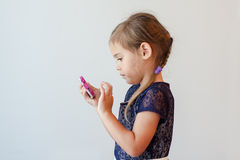 Årig flicka som allvarliga fyra knackar lätt på den smarta telefonen Royaltyfria Foton