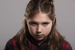 Årig flicka som allvarliga tio ser till kameran, head och skuldror Arkivfoton