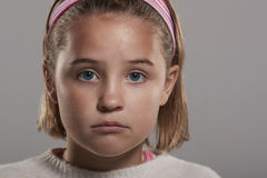Årig flicka som ledsna nio ser till kameran, slut upp huvudskott Arkivbild