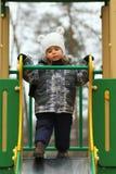 Årig flicka som ledsna två tvekar och ovilligt att glida på vinterlekplatsen Royaltyfri Bild