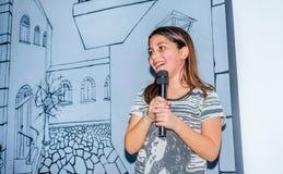 Årig flicka som nio sjunger med mikrofonen Arkivbild
