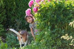 Årig flicka som tre spelar med den gulliga hunden i trädgården Royaltyfria Bilder