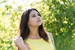 årig flicka som 14 utomhus ser upp på solig dag Arkivfoto