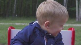 Årig gladlynt pojke som två spelar på en leksakbilgunga portrite stock video