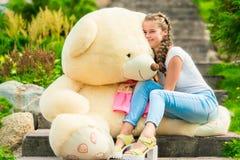 årig lycklig flicka 20 med en stor nallebjörn i parkera på Royaltyfri Bild