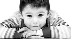 årig lycklig pojke 6 med klockas slag, färgade ögon som framåtriktat lutar med vit bakgrund Royaltyfri Bild
