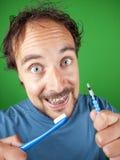 Årig man trettio med hänglsen och en tandborste Royaltyfria Bilder