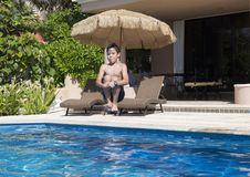 Årig pojke som elva gör en cannonball in i en simbassäng Royaltyfri Fotografi