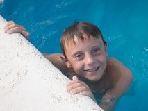 årig pojke som 9 har gyckel i simbassäng Royaltyfri Foto