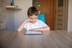 Årig pojke som lite 6 använder minnestavlan, medan sitta på tabellen Fotografering för Bildbyråer