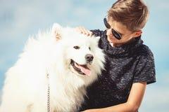 Årig pojke som lyckliga 11 spelar med hans hundavelSamoyed på kusten mot ett slut för blå himmel upp Bästa vän vilar royaltyfri foto