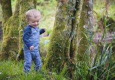 Årig pojke som lyckliga två spelar i en skogsmark Arkivfoto