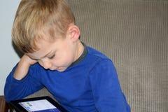 årig pojke som 3 spelar med minnestavlan Arkivbilder