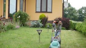 Årig pojke som tio mejar gräsmattan med en stor gräsklippare stock video